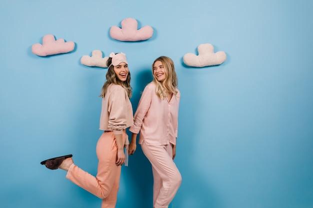 Foto de estúdio de mulheres de pijama em pé na parede azul com nuvens de brinquedo