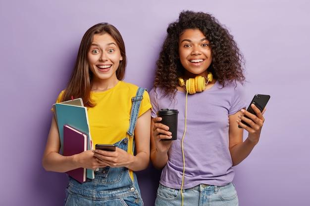 Foto de estúdio de namoradas posando com seus telefones