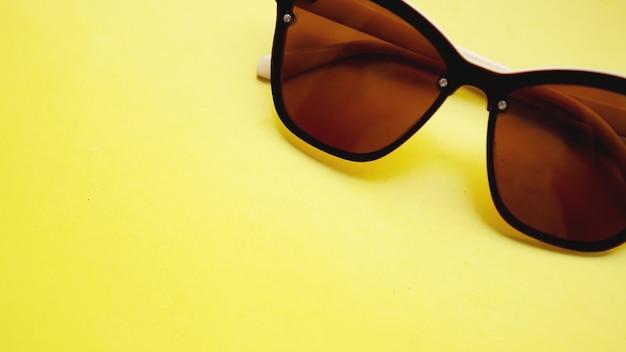 Foto de estúdio de óculos de sol. o verão está chegando - fundo amarelo