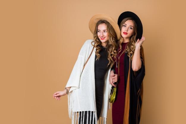 Foto de estúdio de outono de duas modelos com cabelo loiro ondulado em lã e chapéu de palha usando poncho listrado