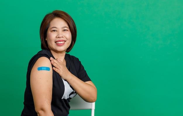 Foto de estúdio de paciente asiático de meia idade sentar sorriso e mostrar atadura de gesso azul no braço após receber a vacinação de coronavírus covid 19 pelo médico na clínica sobre fundo verde.