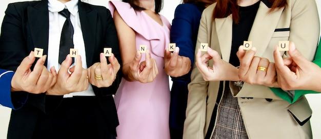 Foto de estúdio de pequeno bloco de cubo de madeira, letras de agradecimento, alfabetos, segurando por funcionários femininos sem rosto não identificados e irreconhecíveis, funcionários do sexo feminino em negócios usam para mostrar apreço aos colegas de clientes.