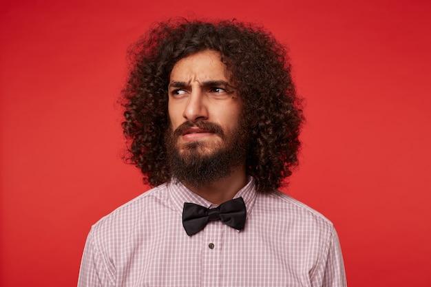 Foto de estúdio de severo moreno encaracolado com barba olhando para o lado e apertando os olhos com as sobrancelhas franzidas, vestido com roupas elegantes enquanto posava contra um fundo vermelho