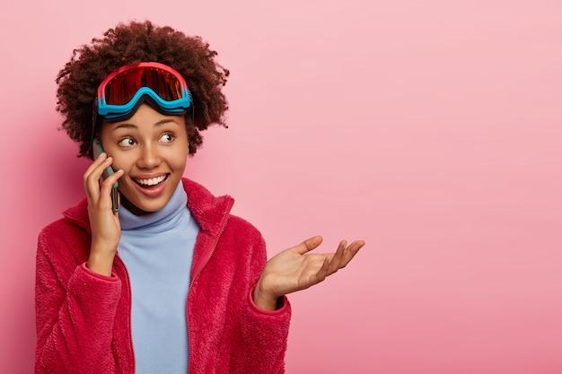 Foto de estúdio de sorrisos e gestos de linda mulher encaracolada feliz, usa óculos de esqui.