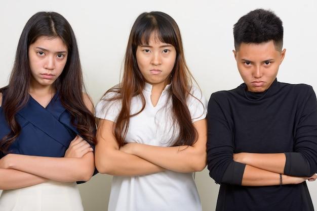 Foto de estúdio de três lindas mulheres asiáticas como amigas contra um fundo branco