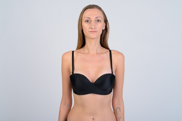 Foto de estúdio de turista mulher loira usando biquíni contra branco