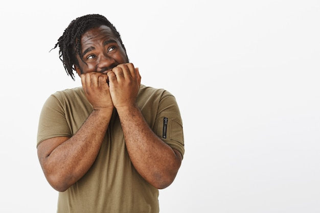 Foto de estúdio de um cara fofo e impaciente com uma camiseta marrom posando contra a parede branca