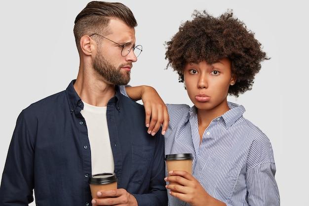 Foto de estúdio de um casal inter-racial intrigado fazendo uma pausa para o café