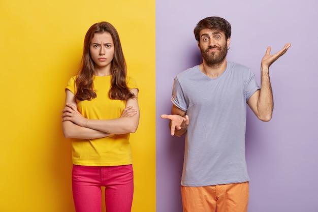 Foto de estúdio de um casal milenar perplexo posando contra a parede de duas cores