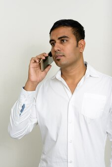 Foto de estúdio de um empresário indiano bonito contra um fundo branco