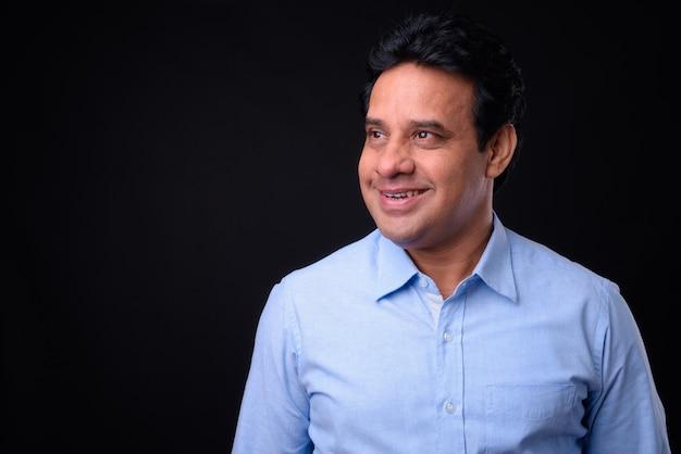 Foto de estúdio de um empresário indiano bonito e maduro contra um fundo preto
