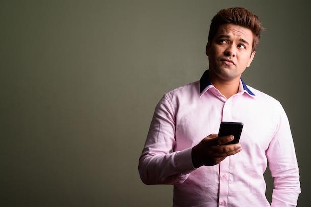 Foto de estúdio de um empresário indiano vestindo uma camisa rosa contra um fundo colorido