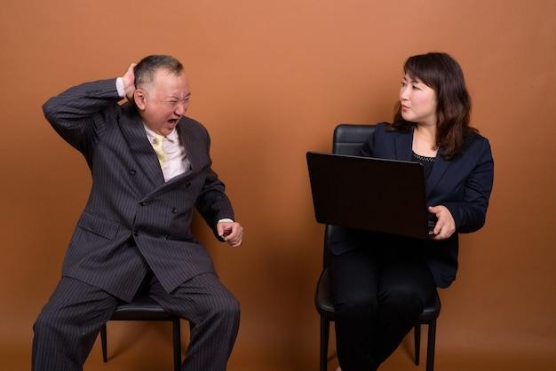 Foto de estúdio de um empresário japonês maduro e uma mulher de negócios japonesa madura juntos contra um fundo marrom