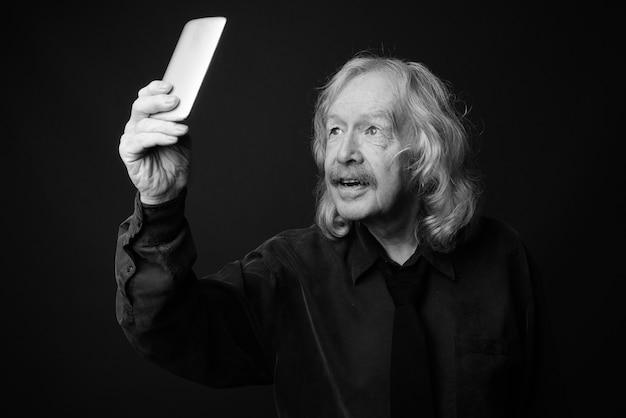Foto de estúdio de um empresário sênior com bigode contra uma parede cinza