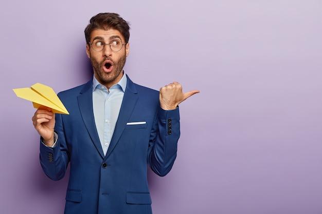 Foto de estúdio de um empresário surpreso posando em um terno elegante no escritório