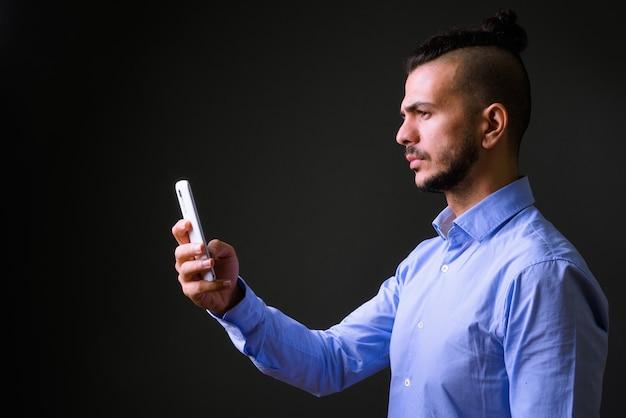Foto de estúdio de um empresário turco bonito usando telefone celular contra um fundo cinza