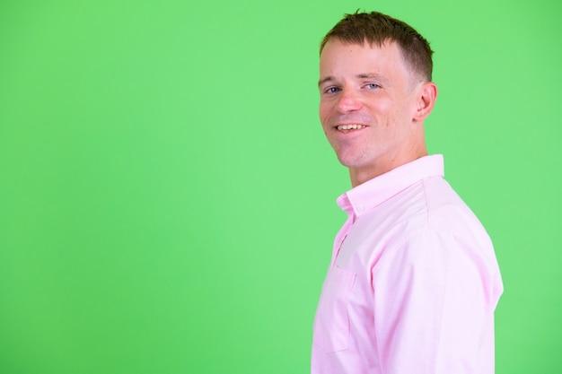 Foto de estúdio de um empresário vestindo uma camisa rosa contra um fundo verde