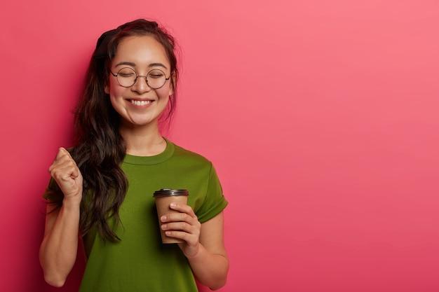 Foto de estúdio de um estudante alegre levanta o punho, regozija-se com o triunfo e conclui a tarefa com sucesso, faz uma pausa para o café após longas horas de trabalho
