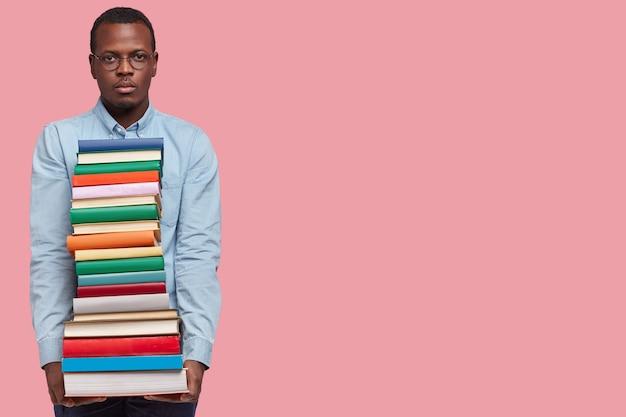 Foto de estúdio de um estudante universitário sério e confiante, de pele escura, carregando muitos livros em uma pilha, usa óculos e camiseta e retorna da biblioteca