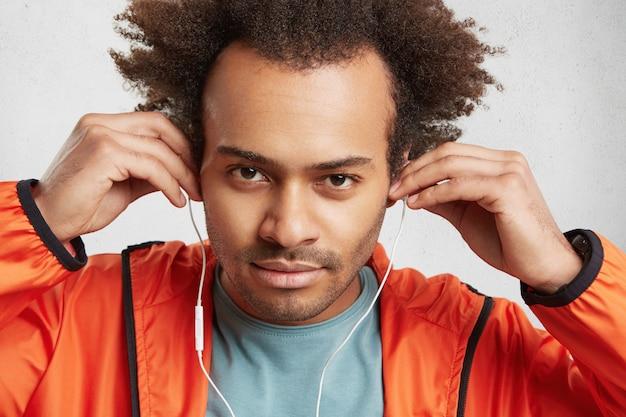 Foto de estúdio de um homem africano de pele escura com uma expressão confiante, coloca fones de ouvido,