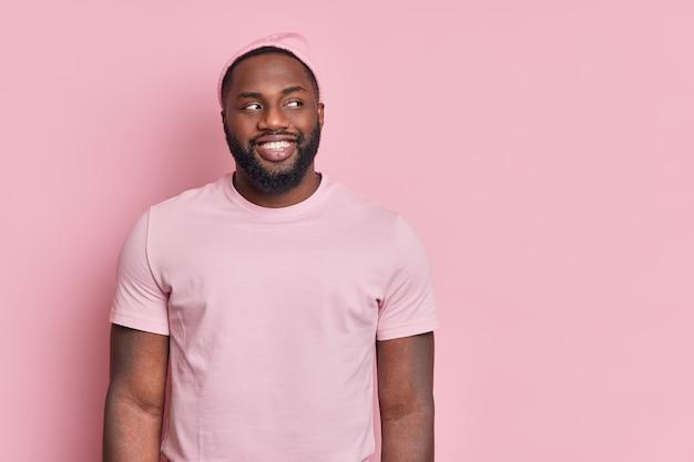Foto de estúdio de um homem afro-americano de pele escura com barba espessa olhando alegremente além de estar de bom humor