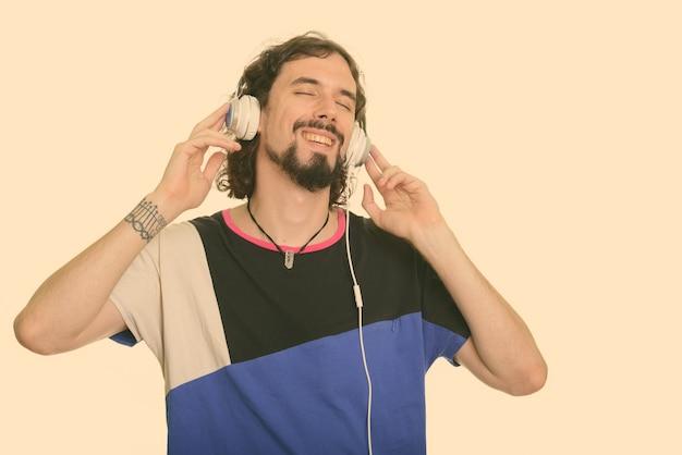 Foto de estúdio de um homem barbudo bonito com cabelo encaracolado isolado no branco