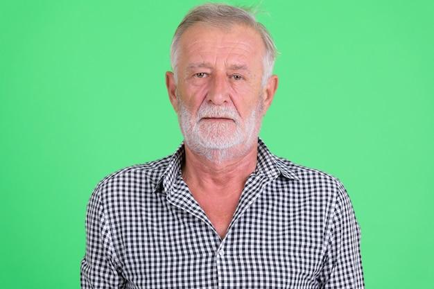Foto de estúdio de um homem barbudo sênior bonito contra um fundo verde