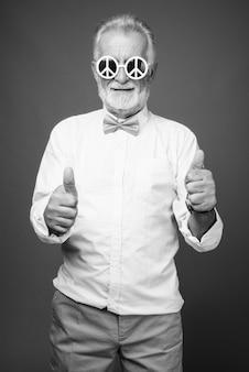 Foto de estúdio de um homem barbudo sênior bonito vestindo roupas elegantes, preto e branco