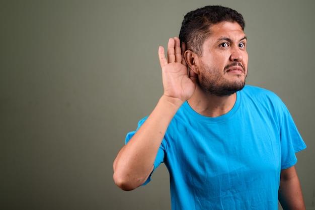 Foto de estúdio de um homem barbudo vestindo uma camisa azul contra cores