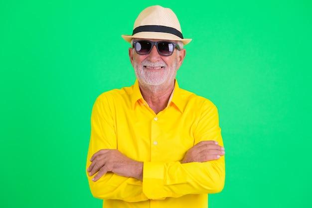 Foto de estúdio de um homem bonito e barbudo turista sênior contra um fundo verde