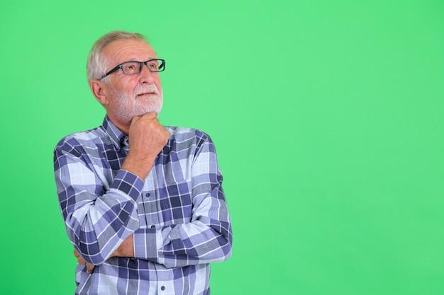 Foto de estúdio de um homem bonito sênior barbudo hippie contra um fundo verde