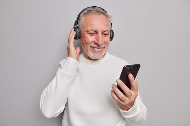 Foto de estúdio de um homem bonito sênior usando aparelhos modernos e ouvindo músicas favoritas com fones de ouvido