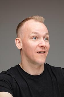 Foto de estúdio de um homem caucasiano de camisa preta parecendo surpreso