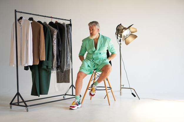 Foto de estúdio de um homem de meia-idade na moda com barba, vestindo uma roupa colorida e elegante, olhando de lado