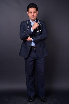 Foto de estúdio de um homem de negócios indiano bonito, maduro, de terno como médico com estetoscópio contra um fundo preto