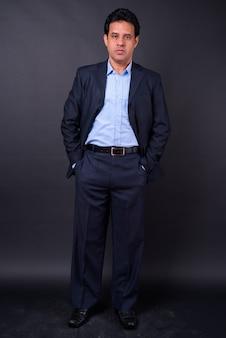 Foto de estúdio de um homem de negócios indiano maduro bonito em um terno contra um fundo preto