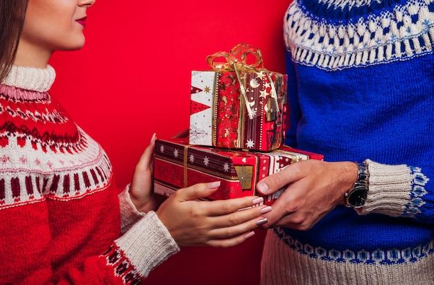 Foto de estúdio de um homem de suéter islandês dando caixas de presente para sua namorada. conceito de comemoração de natal ou ano novo.
