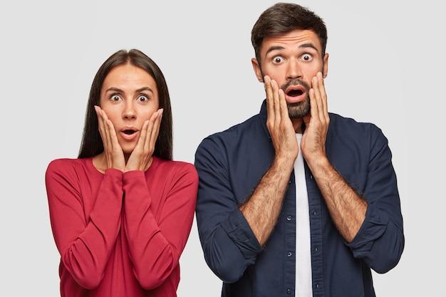 Foto de estúdio de um homem e uma mulher caucasiana emocionada e estupefata com as mãos nas palmas, olhos e bocas bem abertos