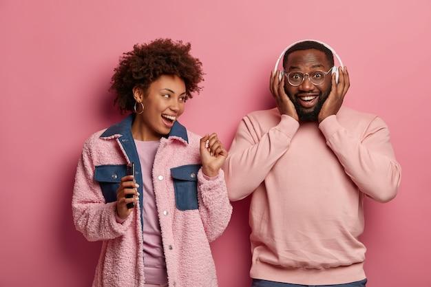 Foto de estúdio de um homem e uma mulher feliz e otimista dançando e se divertindo juntos, vestidos casualmente