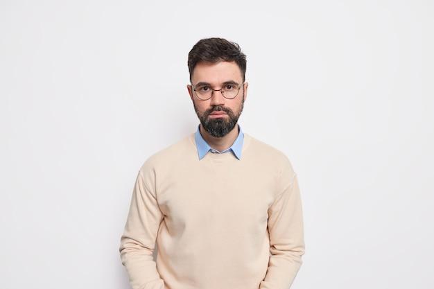 Foto de estúdio de um homem europeu adulto barbudo e bonito olha diretamente, com uma expressão séria e determinado rosto vestido com óculos redondos de macacão elegante