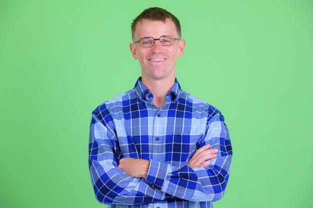 Foto de estúdio de um homem moderno usando óculos contra um fundo verde