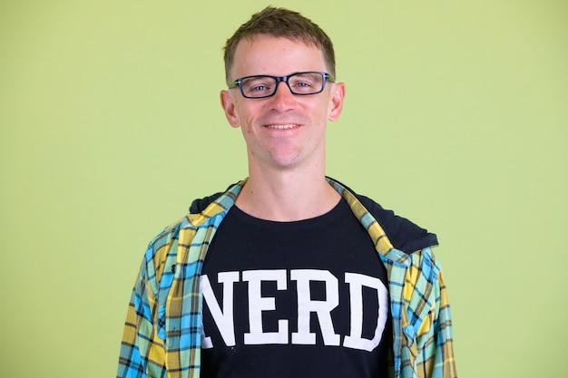 Foto de estúdio de um homem nerd usando óculos contra um fundo colorido