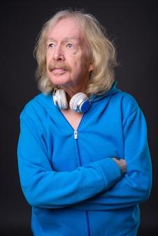 Foto de estúdio de um homem sênior com bigode e jaqueta azul contra um fundo cinza