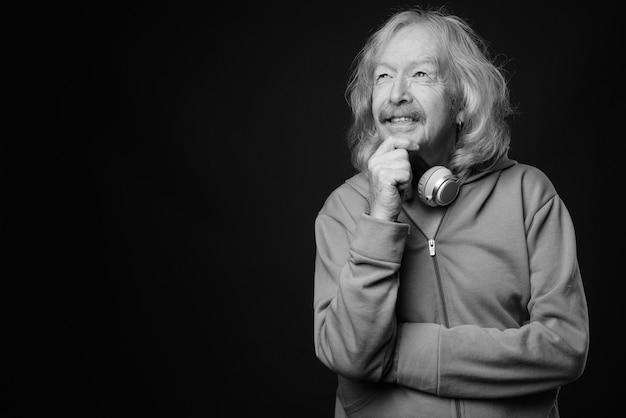 Foto de estúdio de um homem sênior com bigode e jaqueta azul contra uma parede cinza