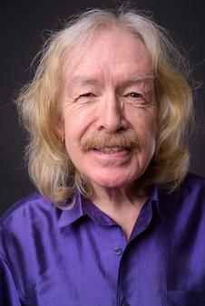 Foto de estúdio de um homem sênior com bigode vestindo uma camisa de seda roxa contra um fundo cinza