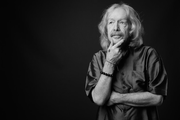 Foto de estúdio de um homem sênior com bigode vestindo uma camisa de seda roxa contra uma parede cinza
