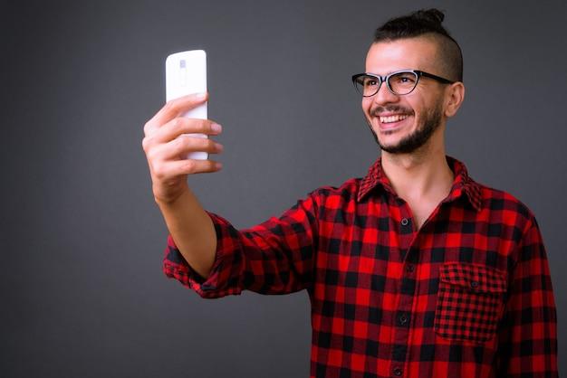 Foto de estúdio de um homem turco bonito usando óculos enquanto usa o telefone celular contra um fundo cinza