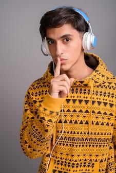 Foto de estúdio de um jovem adolescente persa bonito contra um fundo cinza