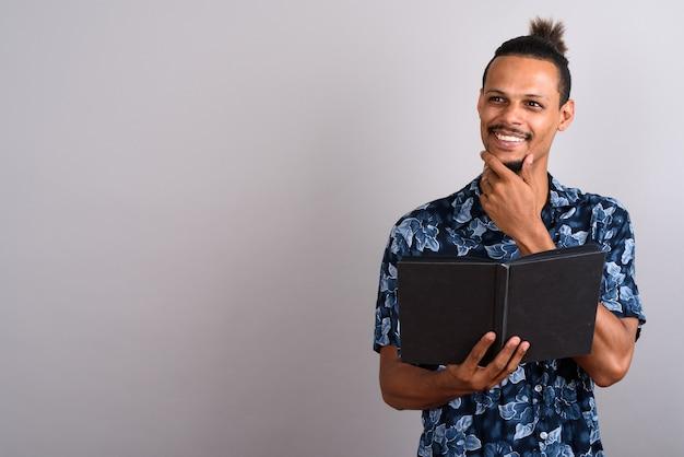 Foto de estúdio de um jovem africano bonito barbudo lendo um livro contra um fundo cinza