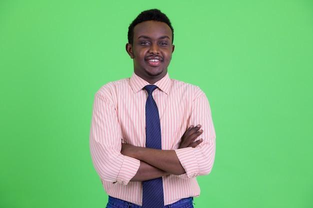 Foto de estúdio de um jovem africano com cabelo afro contra um fundo verde